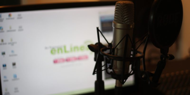 Image of microphone with computer screen in background