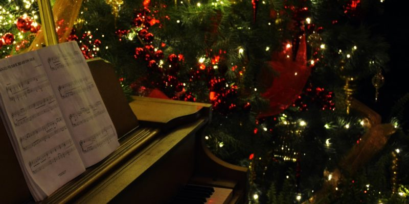 Image of a piano with Christmas sheet music and a Christmas tree in the background.